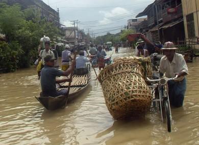 A Myanmar trishaw man wades through a flooded road near Yangon