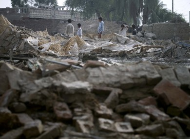 Pakistani youngsters survey the collapsed houses by heavy floodwaters in Lundi village near Karampur, in southern Pakistan.