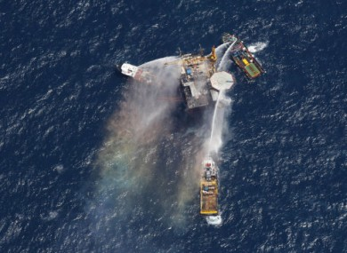 Boats are seen spraying water on an oil and gas platform that exploded in the Gulf of Mexico, off the coast of Louisiana., Thursday, Sept. 2, 2010.