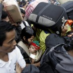 Indonesians struggle to board a ship to leave for their homes on Sumatra island at Tanjung Priok port in Jakarta, Indonesia, Tuesday, Sept. 7, 2010. The mass exodus out of the capital and other major cities in the country is underway as thousands are preparing to head home to their villages to celebrate Eid al-Fitr holiday. The holiday marks the end of the holy fasting month of Ramadan. (AP Photo/Irwin Fedriansyah)