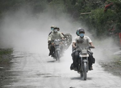 Motorcyclists ride along roads coated with volcanic ash from Mt Sinabung.