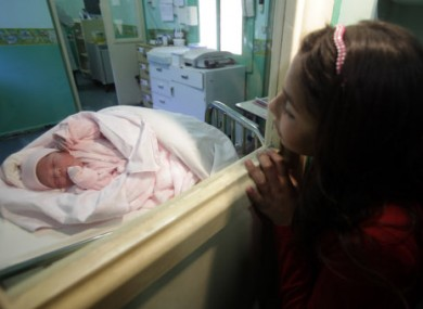 Newborn Esperanza Ticona is watched by her cousin in hospital some 70km from the mine.