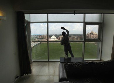 A worker cleans the window of a room in the athlete's village in New Delhi