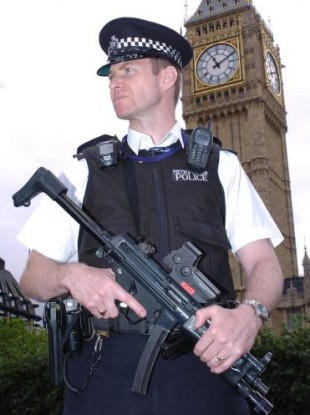 A genuine armed police officer in official uniform on patrol in London.