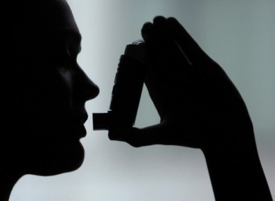 A woman prepares to take a puff from an inhaler.