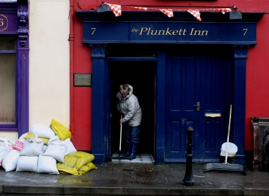 A Cork resident cleans up a pub after floods in the city last November.