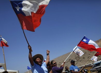 Relatives of trapped miners wave Chilean flags as they welcome vehicles transporting containers to be used as a health center