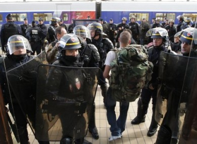 French riot police officers secure the area at the Bordeaux train station, southwestern France, as a passenger arrive during a demonstration against pension reforms, on 22 October, 2010.