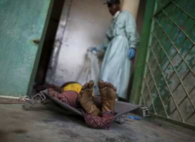 The body of a man that doctors say died of cholera lies on a stretcher at a morgue in Saint Marc, Haiti.