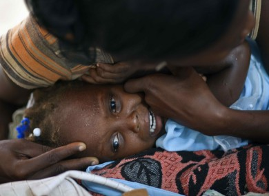A mother comforts her crying daughter, who displays symptoms of cholera, at the hospital in Grande-Saline, Haiti.