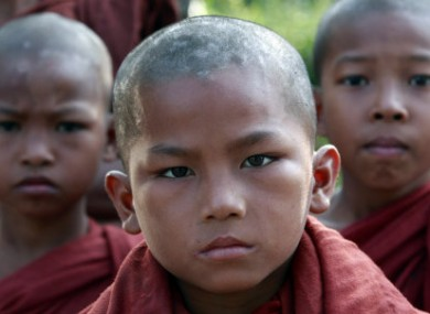 Young Myanmar Buddhist monks wait for food at a Thai border police base where Myanmar refugees have taken shelter in Mae Sot, Thailand, 9 November, 2010.