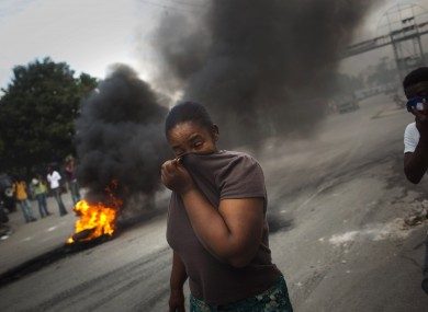 A woman covers her face from the smoke of burning tires set up by demonstrators in Port-au-Prince, who complain that UN peacekeepers are the source of the cholera epidemic sweeping the country.