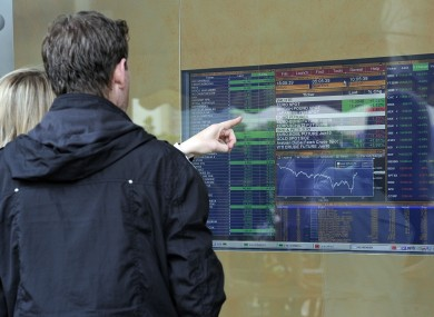 People check a monitor reporting financial data outside a bank in Milan.