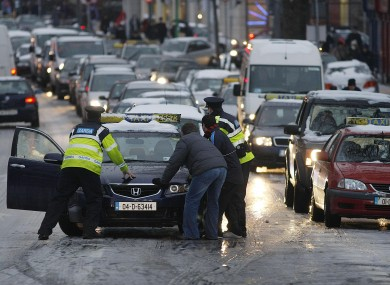 Gardai help motorists deal with icy roads along North Strand during Rush Hour in central Dublin yesterday.
