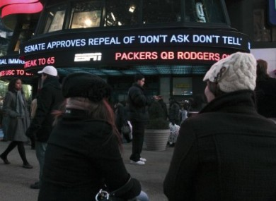 People stop to watch news of the DADT repeal displayed outside ABC Television in Times Square, New York.