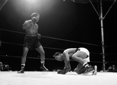Challenger Archie Moore stands over world heavyweight champ Rocky Marciano.