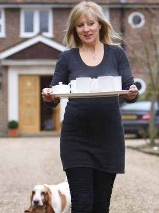 Julia Keys, wife of former Sky Sports presenter Richard Keys, brings a tray of tea to the media waiting outside her Surrey home.