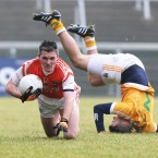 Armagh's John Murtagh takes possession while Antrim's Anto Healey takes a tumble at The Athletics Ground.<span class=