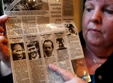 Alice Harper with a press cutting from August 1971 when 11 people, including her father Daniel Teggart, were killed in Ballymurphy, Belfast.