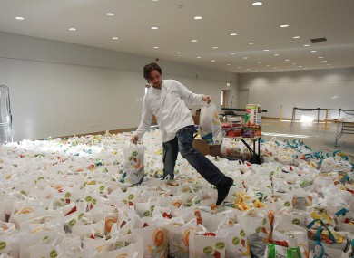 A volunteer fills goodie bags for a Christmas party for the homeless last year.
