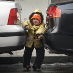A Chinese boy squeezes between two parked cars in Beijing, China where imports of foreign-model cars doubled last year (AP Photo/Andy Wong)