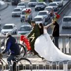 An engaged young Chinese couple sits on a bicycle as they pose for wedding photographs to the theme of naked wedding in Beijing, China. Naked wedding is a popular new expression in China which means young couples get married with no houses, cars or little bank savings. (PA Images/Bao fan)