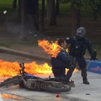 The fire from a Molotov cocktail thrown on a riot police officer in Athens, Greece during this week's protests is damped down by a colleague. Pic: PA Images/Demotix