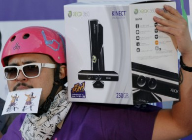 A Japanese first customer poses with a Kinect for Xbox 360 on his shoulder at an electronic chain in Tokyo, 20 November, 2010.