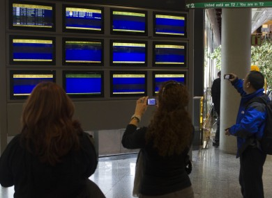 Passengers at Madrid Airpor take photographs of blank departures screens in December, following a wildcat strike by airport staff.