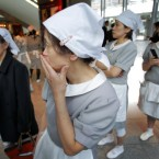 Hotel employees gather at the hotel's entrance in Tokyo, Japan while the earthquake hits. (AP Photo/Itsuo Inouye)