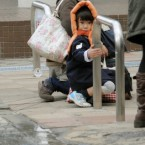 A mother and child crouch in the street as the earthquake hits Tokyo. (PA Images)
