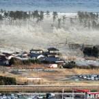 Waves of tsunami hit residences in Natori, Miyagi prefecture. (AP Photo/Kyodo News)