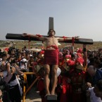 A crowd watches as an unidentified devotee takes part in a re-enactment of the crucifixion of Jesus Christ on Good Friday at Cutud village<span class=
