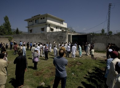 Local people and media gather outside the perimeter wall and sealed gate into the compound and a house where al-Qaida leader Osama bin Laden was caught and killed late Monday, in Abbottabad