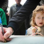 Mary O'Caroll, aged four, watches as her dad Adrian sign the book of condolences for former taoiseach Garret FitzGerald as he lay in state in the Mansion House, Dublin last weekend. (Julien Behal/PA Wire)