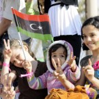 Libyan children flash V signs and hold their old national flag as they attend a rally during an entertainment day in the rebel stronghold of Benghazi. (Image: Demotix)