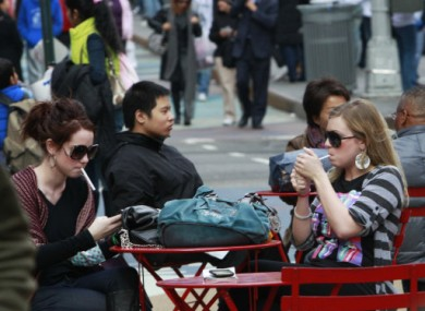 Smokers in Times Square, New York in February - smoking is now banned in pedestrian plazas like this one in the city from today