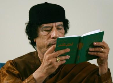 Gaddafi reads his Green Book.