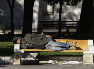 File photo of an unidentified homeless man sleeping on a park bench.