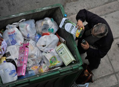 A man empties out the remains of an olive oil container before dumping it in the Greek city of Thessaloniki. S&P now deems Greek government bonds firmly in 'junk' territory.