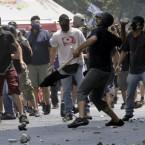 Protesters throw stones at riot police. Pic: AP Photo/Petros Giannakouris