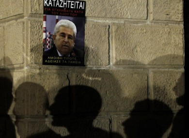 The silhouettes of protesters on a wall with a poster of Cyprus' president Dimitris Christofias that reads in Greek