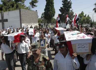 Syrian policemen carry the coffins of police and army members who were believed killed in recent violence in Homs, Syria