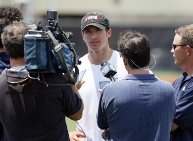 New Orleans Saints quarterback Drew Brees, center, speaks with reporters after a player-organized practice at Tulane University in New Orleans this morning.