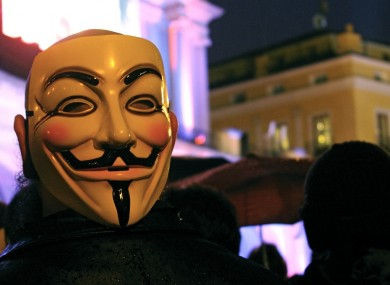 An Anonymous supporter wears the mask associated with the group