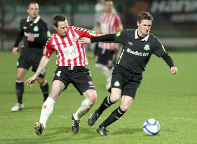 Derry City's Barry Molloy and Gary Twigg of Shamrock Rovers face off during last March's game at the Brandywell, when a Rovers' fan bus was attacked.