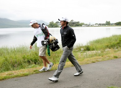orthern Ireland's Rory McIlroy with caddy JP Fitzgerald make their way to third green yesterday.