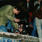 A man on top of the Wall near the Brandenburger Gate chisels a piece of the Wall on November 10.   People scrambled to the barrier on November 9 when East German Politburo member Günter Schabowski declared that travel restrictions for residents would begin