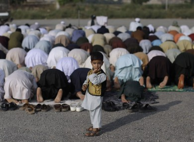 A Pakistani boy looks on while standing in front of worshippers praying during the first day of Eid al-Fitr festival