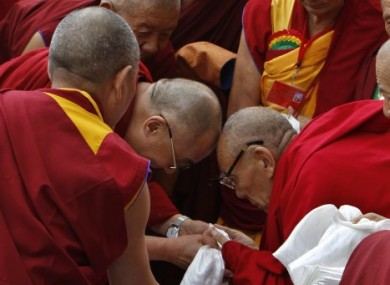 Tibetan spiritual leader the Dalai Lama, centre left, greets a monk as he arrives to attend  an event in India last summer.